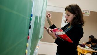 Une institutrice écrit au tableau dans sa classe