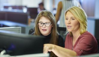 Personne en situation de handicap en train de travailler sur un ordinateur avec son employeur