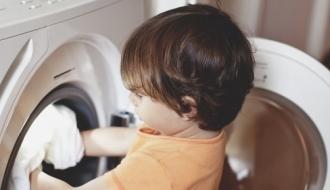 Un enfant manipulant du linge dans un lave-linge