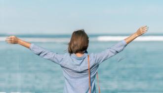 Une femme fait face à la mer en ayant les bras tendus et levés vers l'horizon
