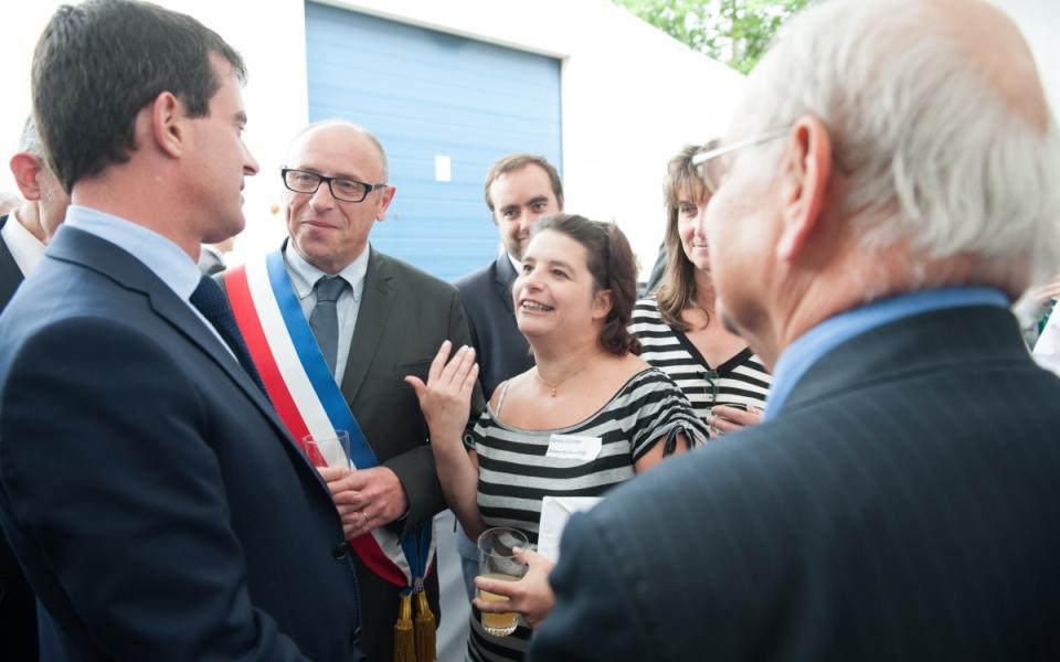 Manuel Valls échange avec le maire de Gasny, Pascal Jolly, et une employée de l'entreprise SAB.