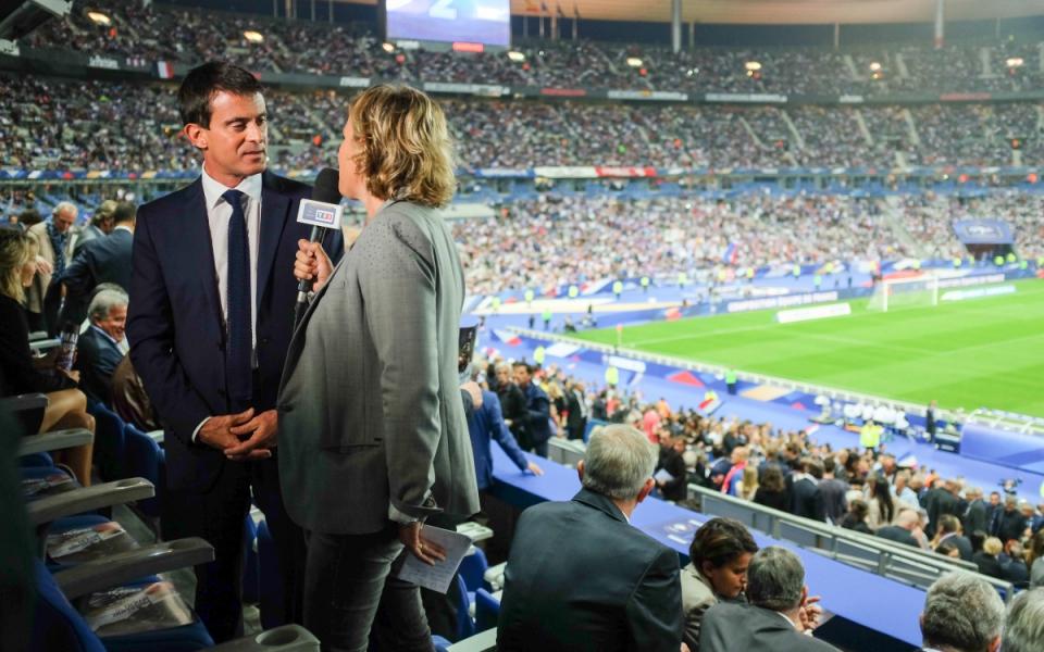 Manuel Valls interviewé par une journaliste avant le coup d'envoi du match amical France-Espagne.