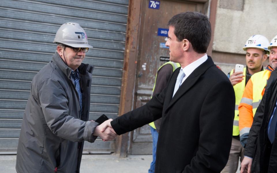 Manuel Valls salue des ouvriers du bâtiment dans les rues de Cachan