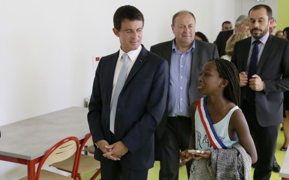 Manuel Valls à l'école Aimé Césaire d'Evry accompagné d'une jeune membre du Conseil municipal des enfants