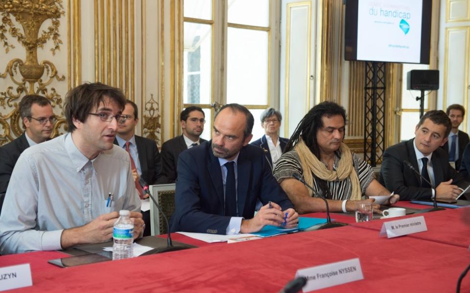 Le Premier ministre, Édouard Philippe, écoute la prise de parole de Josef Schovanec, représentant des personnes avec autisme. À la droite d'Édouard Philippe, Ryadh Sallem, handi-basketteur et vice-président de l'Agence pour l'éducation par le sport.
