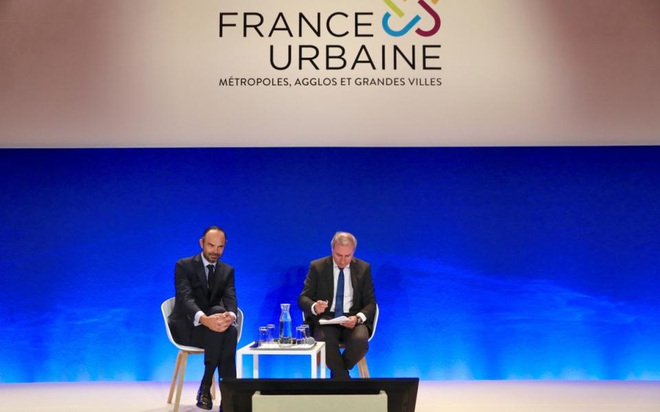 Sur le plateau de la Conférence des Villes-France Urbaine.  Le Premier ministre, Édouard Philippe aux côtés de Jean-Luc Moudenc, président de France Urbaine.