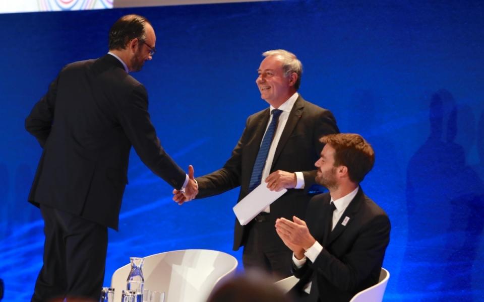 Édouard Philippe salue le président de France Urbaine, Jean-Luc Moudenc. À droite de l'image, Bruno Juliliard, adjoint au maire de Paris