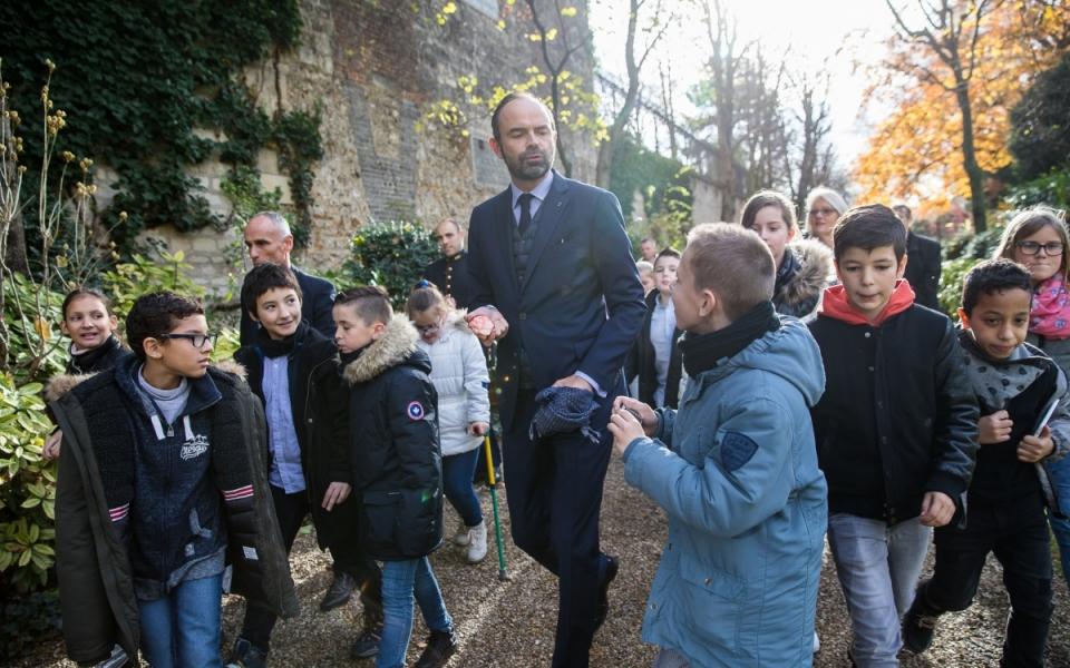 Édouard Philippe et les enfants de CM2 retournent à l'intérieur de lHôtel de Matignon après le planter de l'arbre.