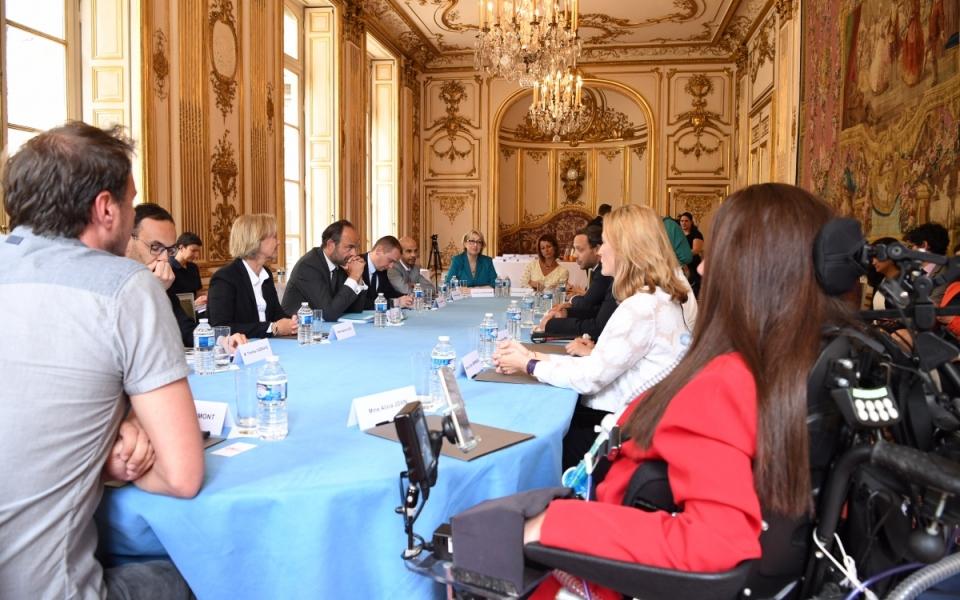 Le Premier ministre, Édouard Philippe, en discussion avec les co-auteurs du rapport, Adrien Taquet, député, et Jean-François Serres, membre du Conseil économique, social et environnemental et des personnes en situation de handicap ayant été auditionnées dans le cadre du rapport et des personnes agissant dans le domaine du handicap.