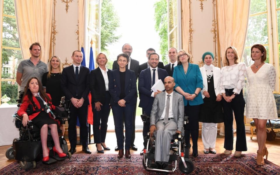 Le Premier ministre, Édouard Philippe, avec les co-auteurs du rapport, Adrien Taquet, député, et Jean-François Serres, membre du Conseil économique, social et environnemental, des personnes en situation de handicap ayant été auditionnées dans le cadre du rapport et des représentants du monde du handicap.