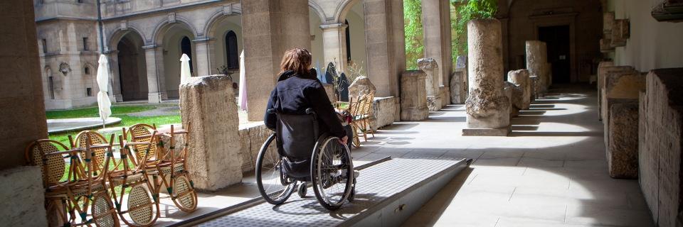 Photo d'une personne en fauteuil roulant se déplaçant sur une rampe d'accessibilité