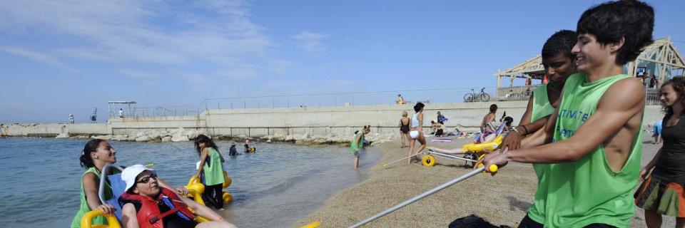 Photo de jeunes volontaires aidant une femme handicapée à prendre un bain de mer.