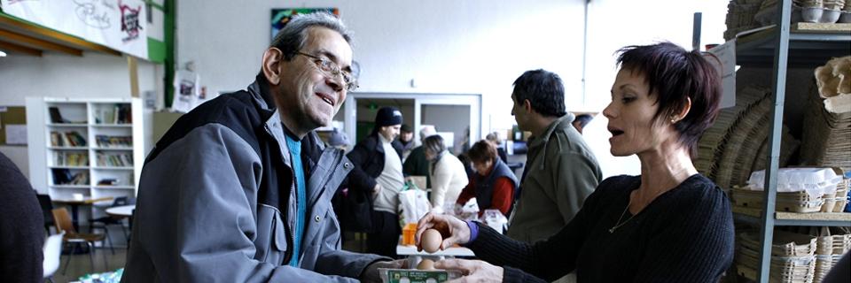 Photo d'un homme recevant des oeufs d'une bénévole aux Restos du Coeur.
