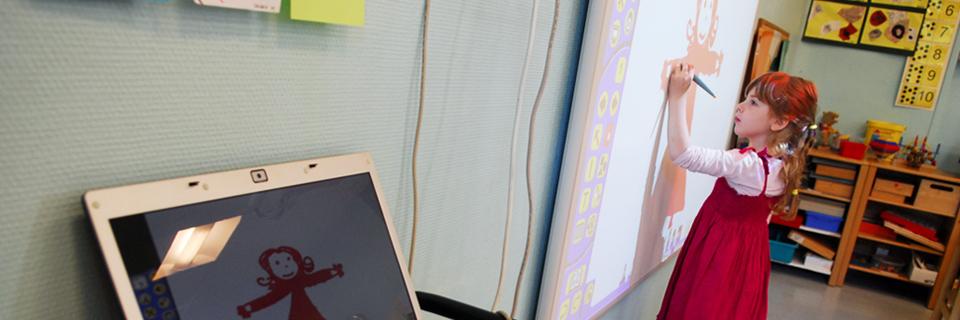 Photo d'une écolière de maternelle utilisant un Tableau Blanc Interactif (TBI) qui remplace petit à petit les vieux tableaux noirs et la craie.
