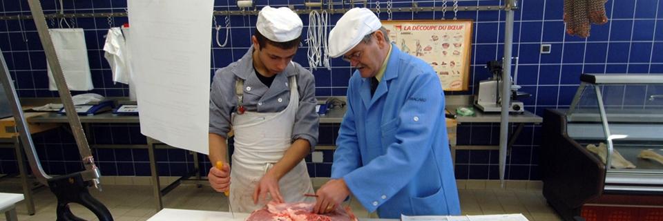 Photo d'un apprenti boucher écoutant un formateur
