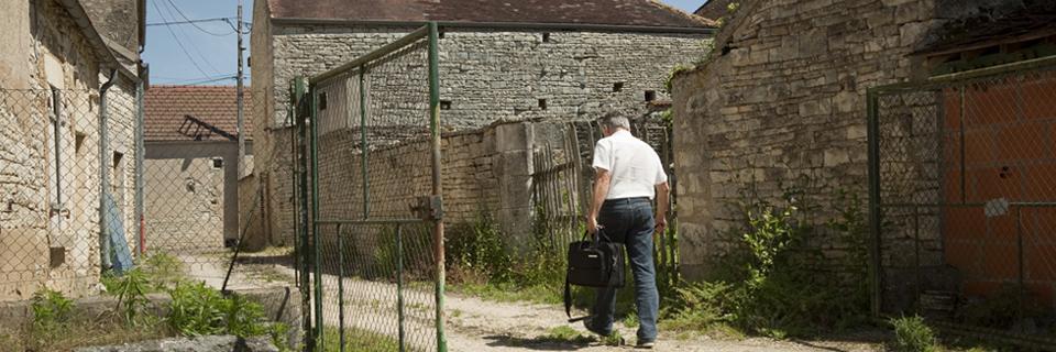 Photo d'un médecin de campagne sortant de chez un patient.