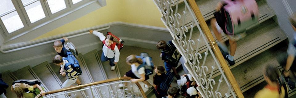 Photo d'élèves remontant un escalier pour accéder à leur classe un jour de rentrée scolaire.