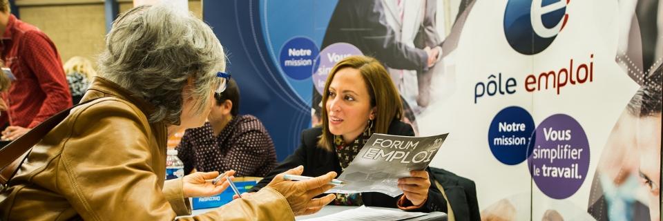 Photo d'une employée de Pôle emploi donnant des conseils à une femme lors d'un salon pour l'emploi à Villeneuve-d'Ascq le 30 septembre 2014.