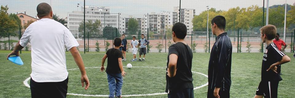 Photo d'un éducateur sportif prodiguant un cours de football à des enfants