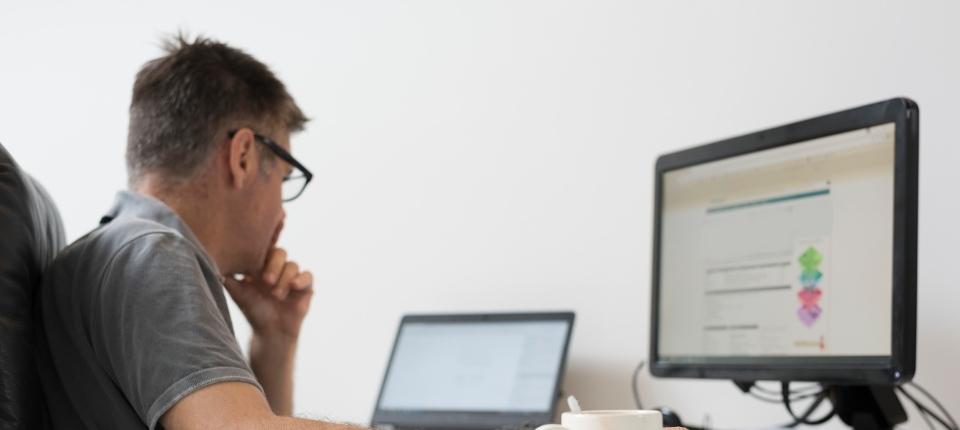 Une personne travaille devant son ordinateur