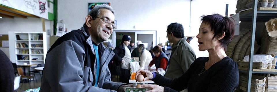 Un homme reçoit des oeufs de la part d'une bénévole des Restos du coeur