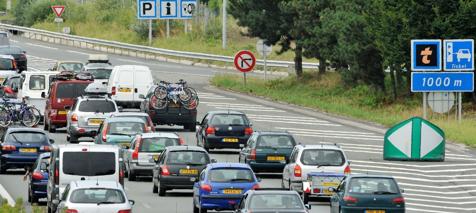 Photo d'automobiles arrivant à un péage autoroutier un jour de grands départs.