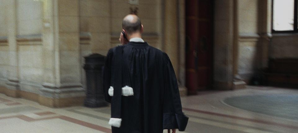 Photo d'un avocat en robe dans un tribunal.