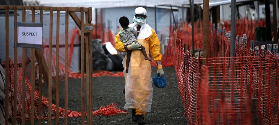 Photo d'un soignant dans sa tenue stérile, portant un enfant dans ses bras, dans un centre de traitement Ebola de MSF au Liberia.