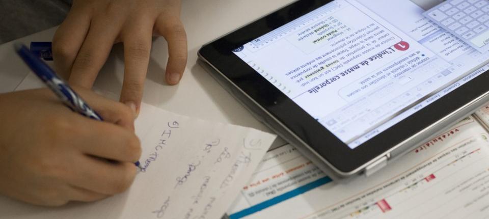 Photo d'un élève travaillant avec un manuel scolaire et une tablette.