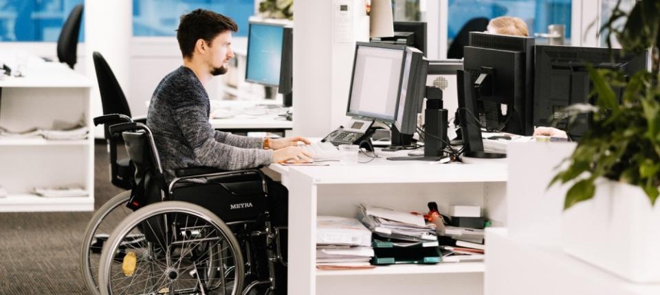 photo d'un homme en fauteuil roulant travaillant dans un open space en entreprise avec d'autres collègues n'ayant pas de handicap visible