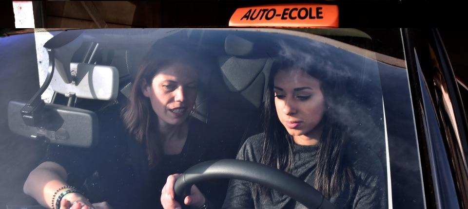 Une personne passant son permis de conduire avec son instructeure