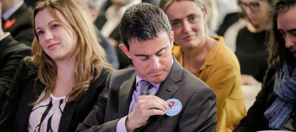 Photo du Premier ministre, prise le 4 octobre 2014 au Numa à Paris pour le lancement de la concertation nationale sur le numérique. Manuel Valls assis à côté d'Axelle Lemaire colle sur sa veste l'autcollant appelant à contribuez.