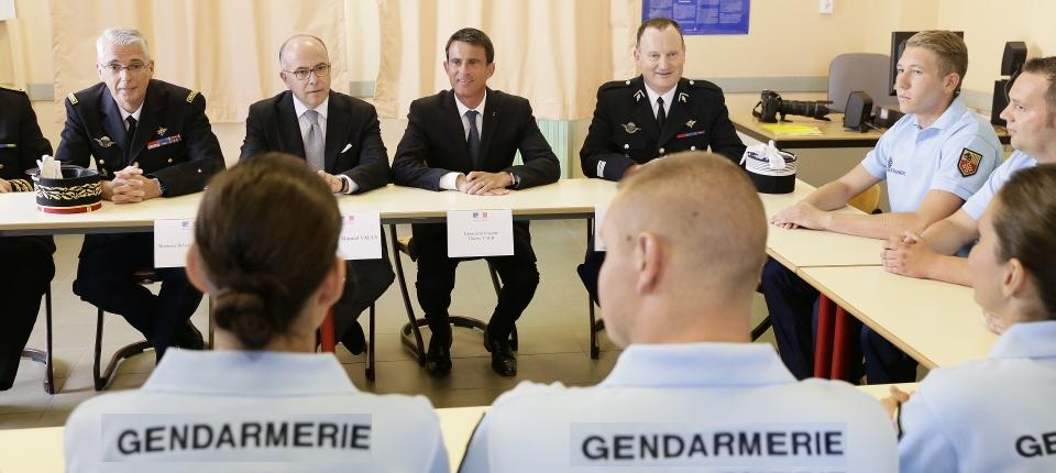 Photo de Manuel Valls et Bernard Cazeneuve échangeant avec des élèves réservistes à l'école de gendarmerie de Montluçon le 11 août 2016.
