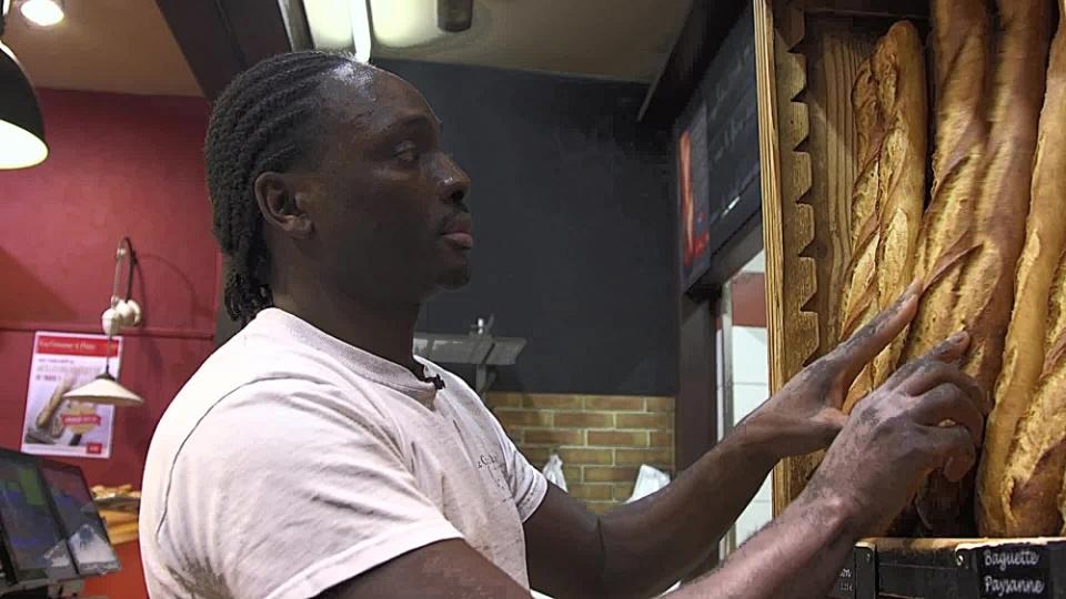 Djibril Bodian disposant ses baguettes sur le présentoir de sa boulangerie