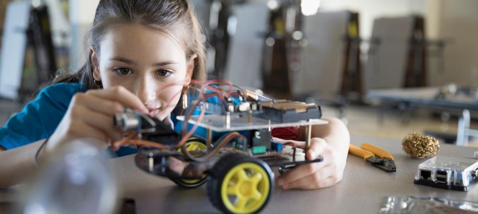 Une collégienne en entreprise en train de construire un robot