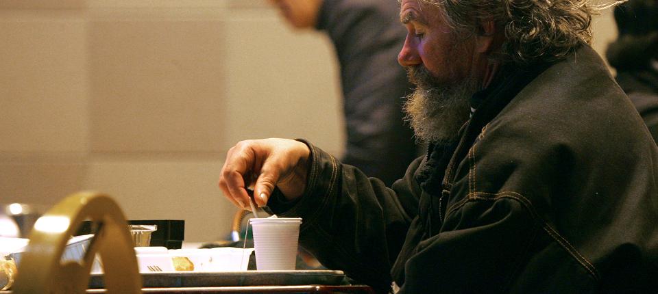 Un SDF dîne dans un centre d'hébergement d'urgence pour les personnes sans-abri