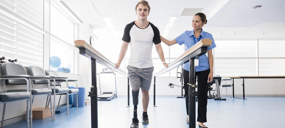 Un homme amputé avec une jambe en prothèse s'entraîne à marcher avec sa kynésithérapeute