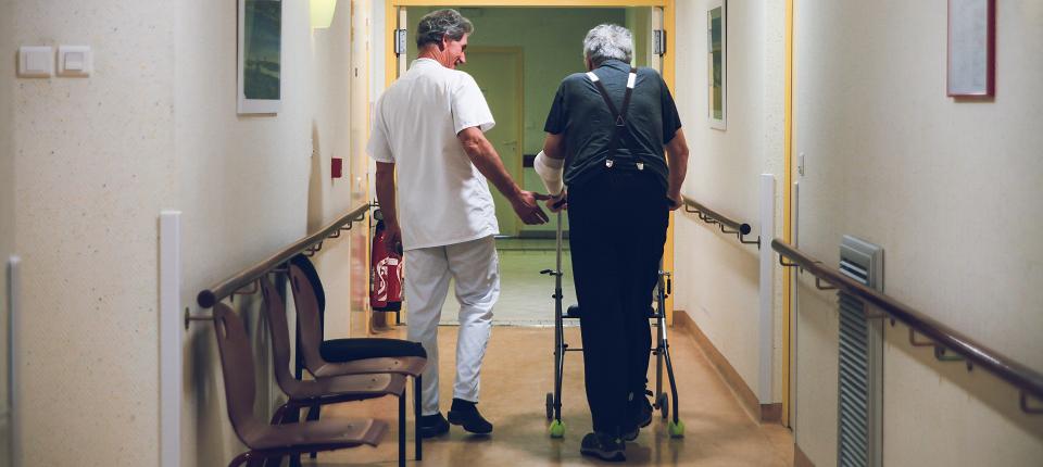 Médecin aidant un monsieur âgé à marcher avec son déambulateur dans le couloir d'un hôpital