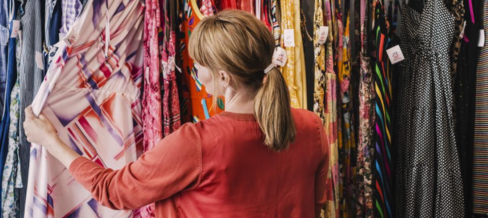 Une femme regarde des vêtements dans un magasin