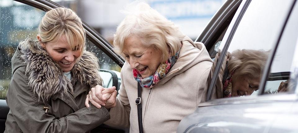 Une jeune femme aide une personne âgée à sortir de voiture