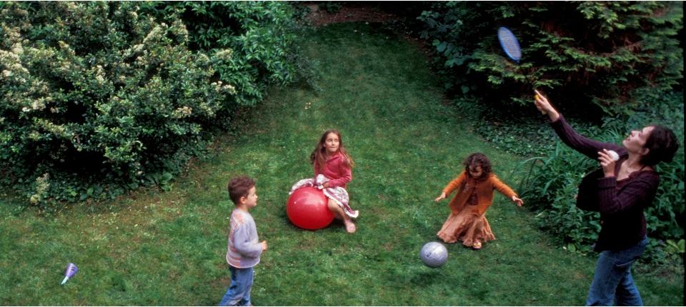 Enfants jouant dans un jardin avec leur monitrice