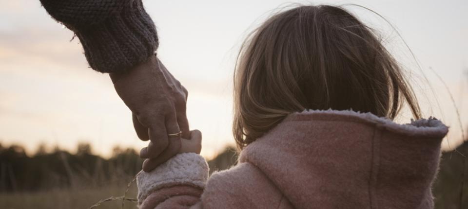 Une enfant tient une main d'adulte
