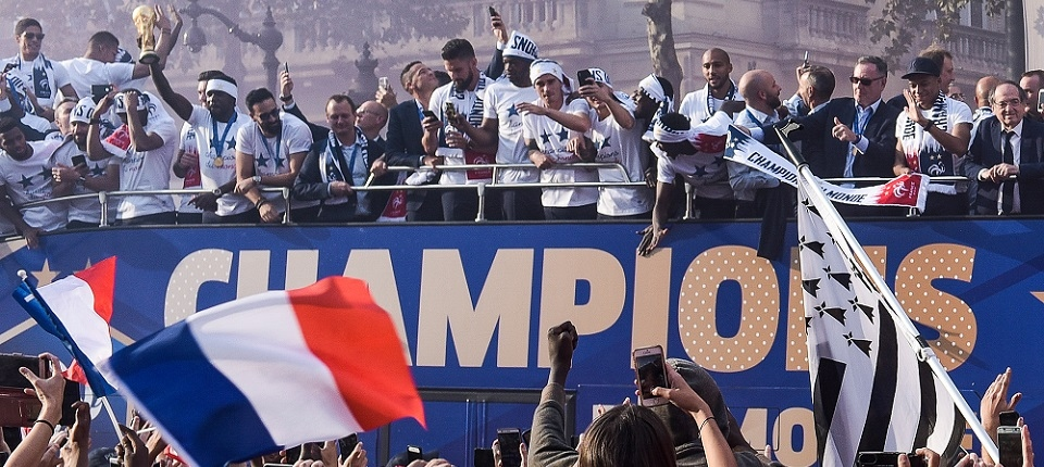 France's defender Samuel Umtiti (4th L) holds the trophy as he celebrates with teammates on the roof of a bus while parading down the Champs-Elysee avenue in Paris, on July 16, 2018