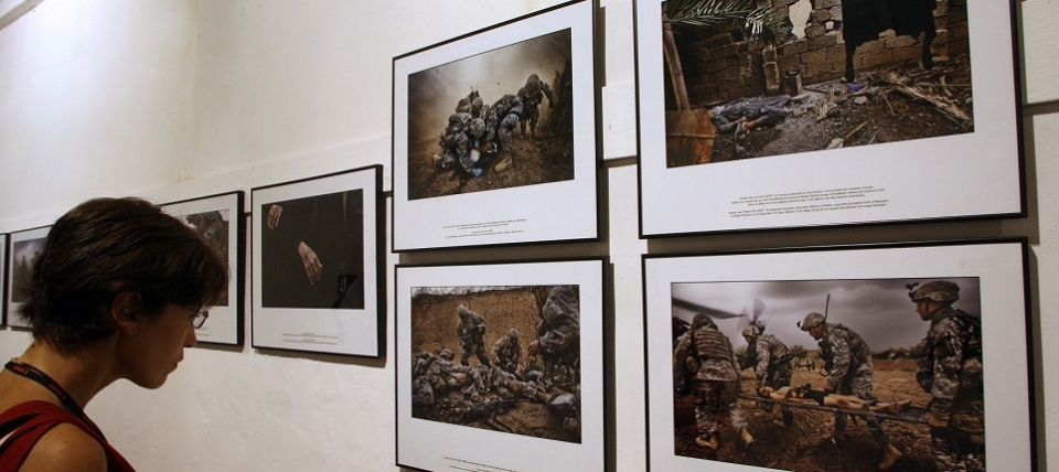 A woman looks at pictures of photojournalist Yuri Kozyrev about the conflict in Iraq (2008)