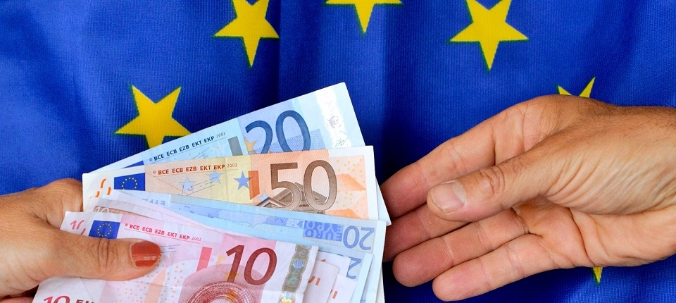 2 hands exchanging euros in front of the European Union flag.