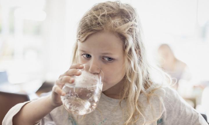 Une fillette boit un verre d'eau
