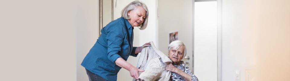 Une femmes en aide une autre à s'habiller