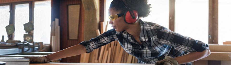 Une jeune femme en formation dans un atelier d'ébénisterie