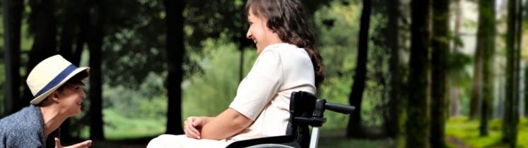 Žena na vozíku se baví s přítelem.