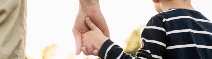 Un père tient son fils par la main